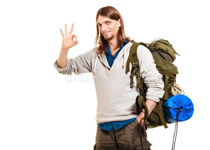 Viaggiatore con zaino e sacco a pelo turistico dell'uomo che mostra gesto giusto Corsa immagini stock