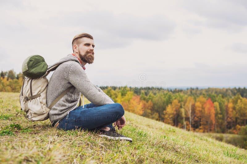 Viaggiatore del giovane che si siede sopra la collina concetto di stile di vita dell'attivo e di viaggio fotografia stock libera da diritti