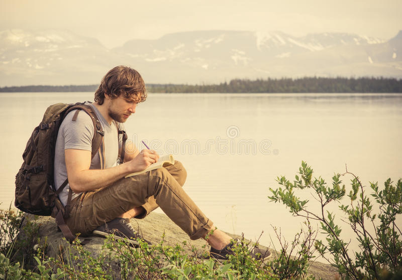 Viaggiatore del giovane con il libro di lettura dello zaino immagine stock libera da diritti