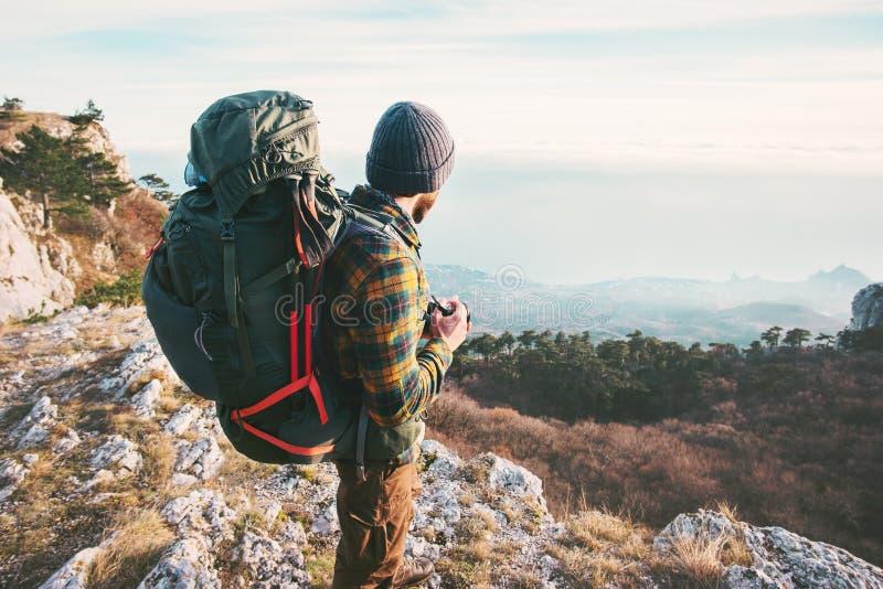 Viaggiatore dell'uomo con lo zaino che fa un'escursione le montagne fotografia stock