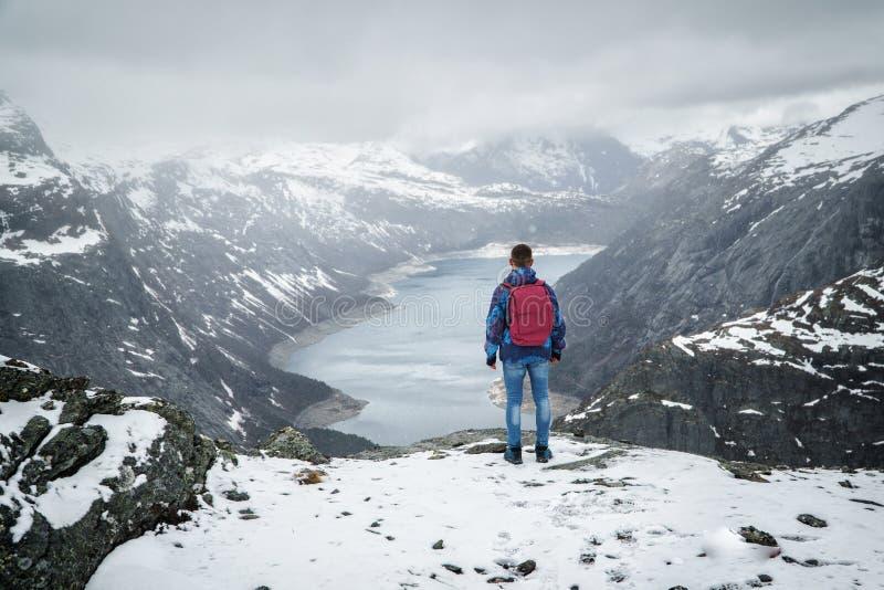 Viaggiatore dell'uomo con lo zaino che sta indietro sul bordo e che esamina il paesaggio della montagna di paesaggio sotto la nev fotografie stock