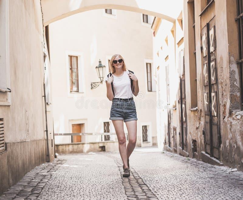 Viaggiatore della donna che cammina attraverso la galleria in città storica europea Ragazza dei pantaloni a vita bassa che viaggi fotografie stock libere da diritti