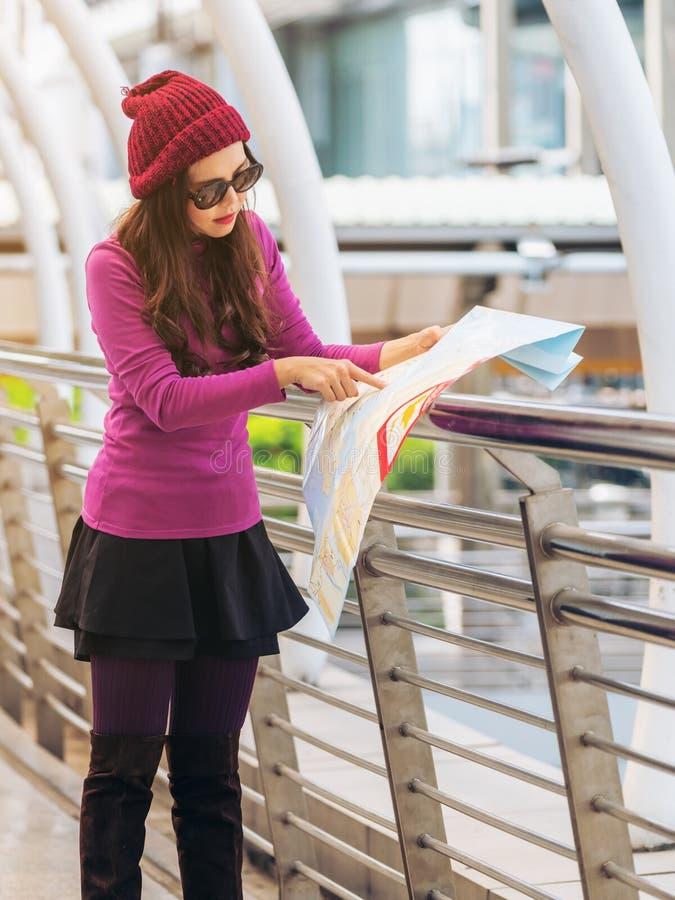 Viaggiatore della donna che esamina la mappa di viaggio fotografia stock libera da diritti