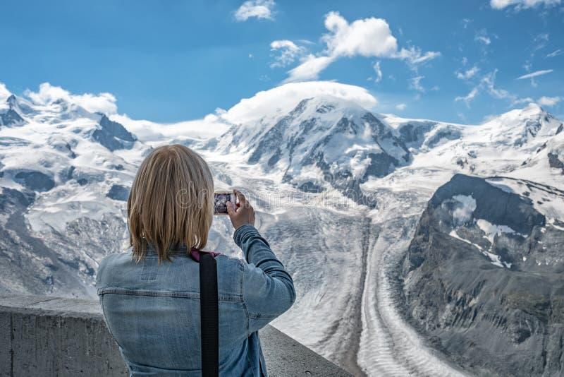 Viaggiatore della donna che prende foto delle montagne fotografie stock