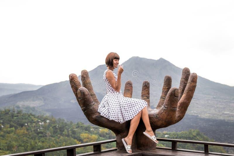 Viaggiatore della donna con la tazza di caffè caldo su un fondo della montagna Volcano Batur, isola di Bali l'indonesia immagini stock