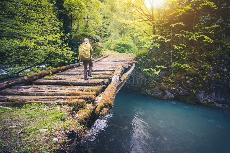Viaggiatore della donna con lo zaino che fa un'escursione sul ponte sopra il fiume fotografie stock