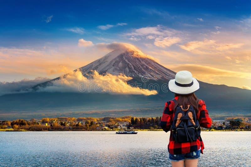 Viaggiatore della donna con lo zaino che osserva alle montagne di Fuji il tramonto nel Giappone fotografia stock