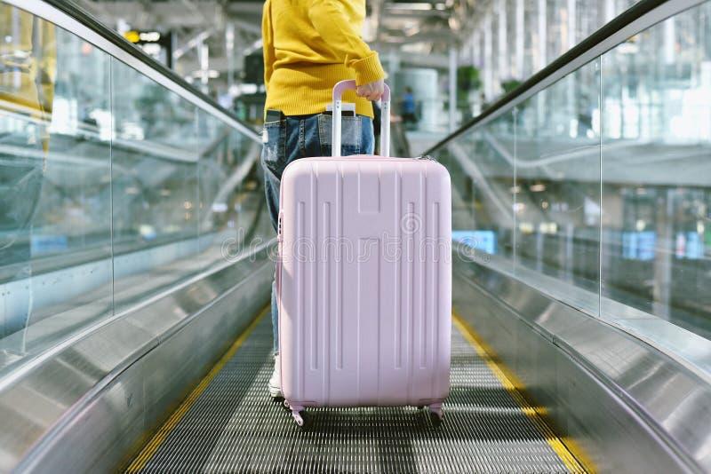 Viaggiatore della donna portare grande valigia sul passaggio pedonale della scala mobile al terminale di aeroporto fotografia stock libera da diritti