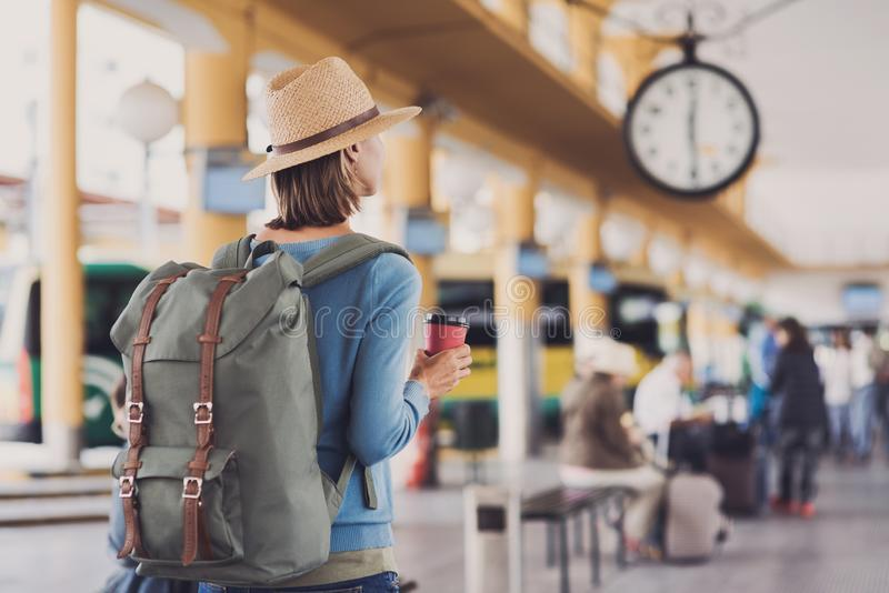 Viaggiatore della giovane donna che aspetta un bus su un'autostazione, su un viaggio e su un concetto attivo di stile di vita immagini stock