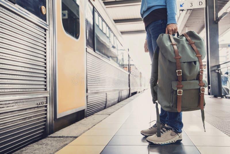 Viaggiatore della giovane donna che aspetta un treno su una stazione ferroviaria, su un viaggio e su un concetto attivo di stile  fotografia stock