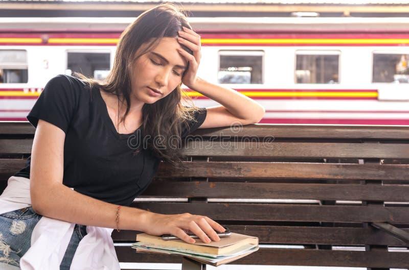 Viaggiatore della giovane donna che dorme alla stazione ferroviaria fotografia stock libera da diritti