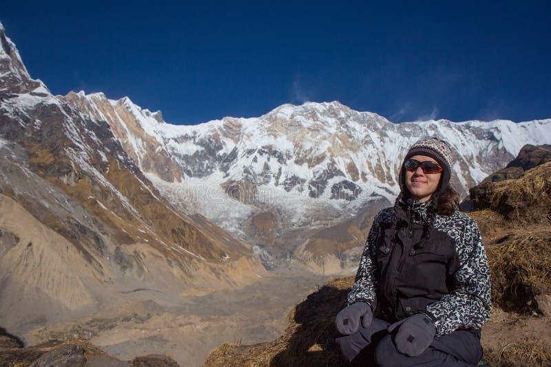 Viaggiatore della giovane donna che si siede davanti alle montagne dell'Himalaya fotografia stock