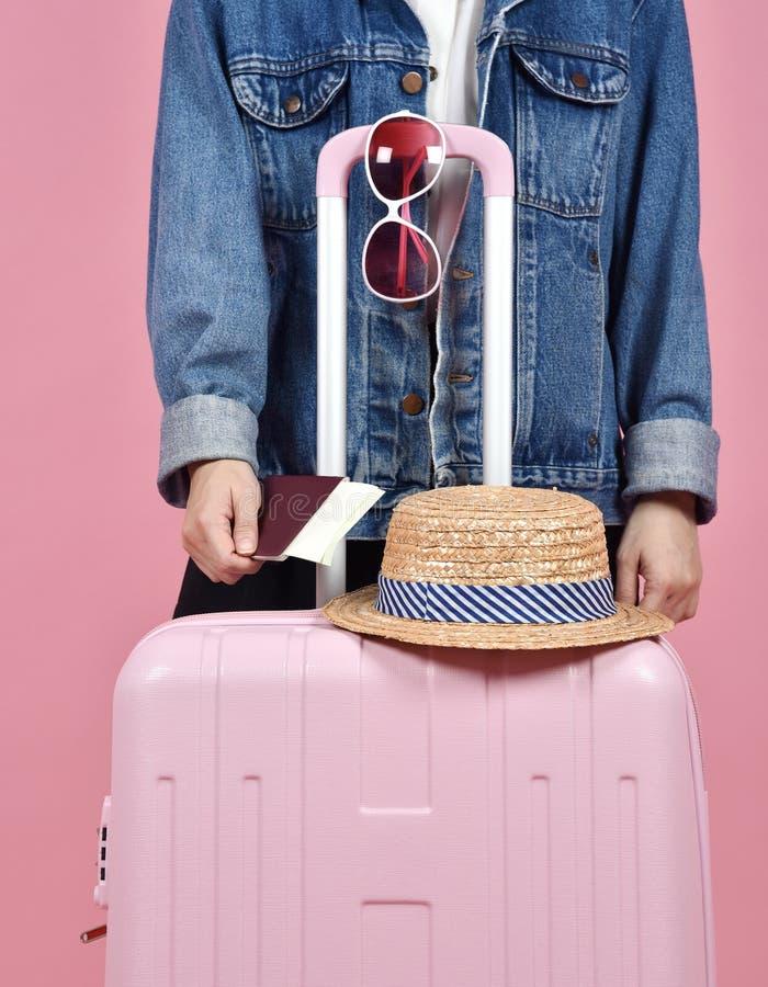 Viaggiatore della giovane donna che tiene il documento rosa del passaporto e della valigia sopra fondo rosa immagine stock