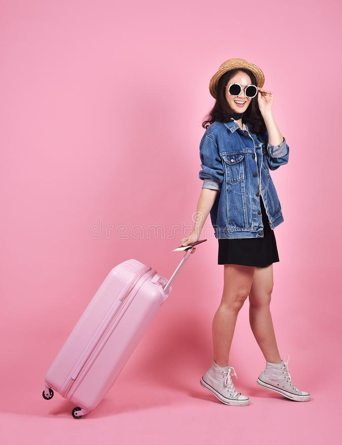 Viaggiatore della giovane donna che tiene il documento rosa del passaporto e della valigia sopra fondo, il viaggio ed il viaggio  immagini stock libere da diritti
