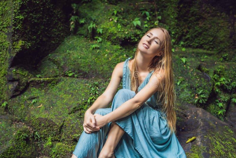Viaggiatore della giovane donna in un giardino di balinese invaso con muschio Viaggio al concetto di Bali fotografie stock