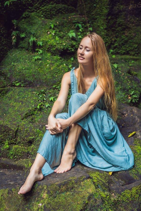 Viaggiatore della giovane donna in un giardino di balinese invaso con muschio Viaggio al concetto di Bali immagine stock libera da diritti