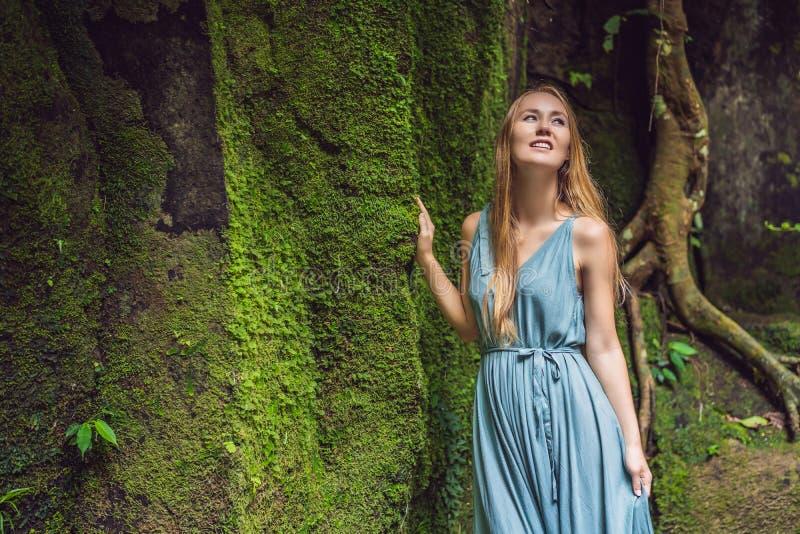 Viaggiatore della giovane donna in un giardino di balinese invaso con muschio Viaggio al concetto di Bali immagini stock libere da diritti