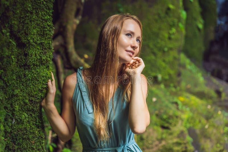 Viaggiatore della giovane donna in un giardino di balinese invaso con muschio Viaggio al concetto di Bali immagine stock