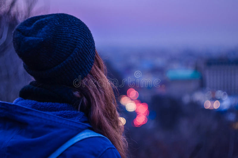 Viaggiatore della ragazza dei pantaloni a vita bassa che esamina paesaggio urbano di sera di inverno, cielo viola e le luci vaghe fotografia stock libera da diritti
