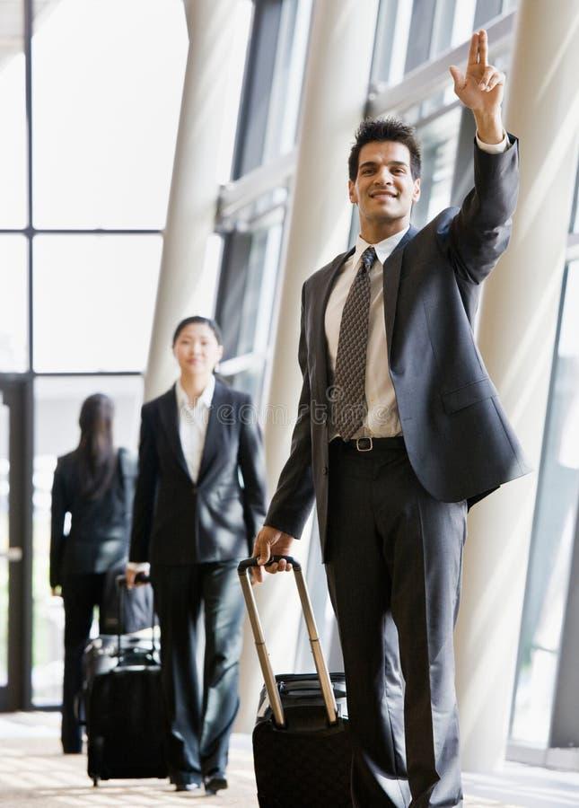 Viaggiatore di affari che tira valigia e gesturing
