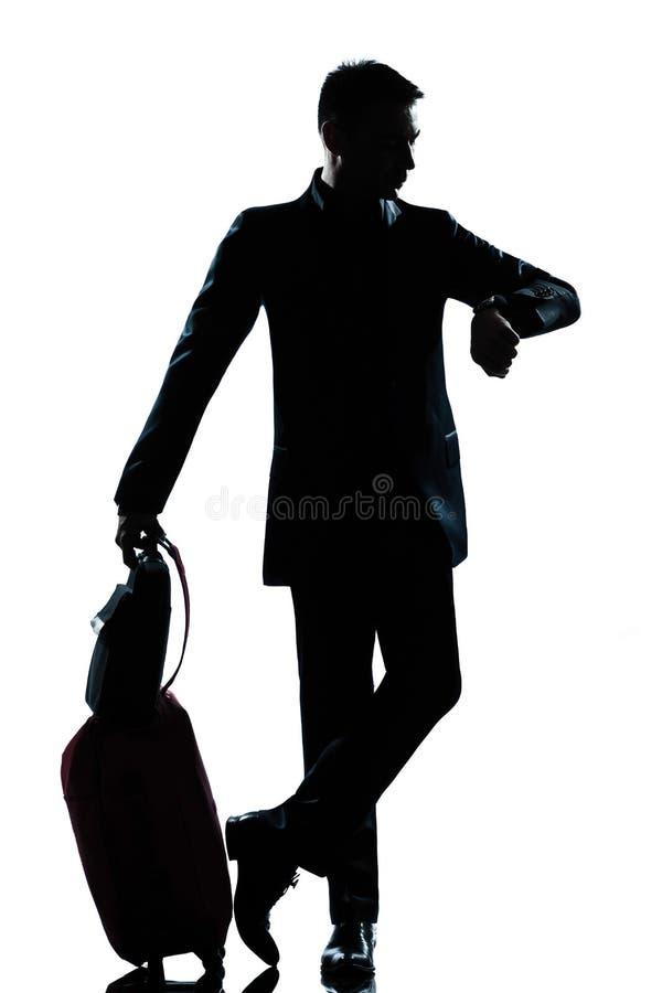 Viaggiatore di affari dell'uomo della siluetta che controlla il tempo fotografia stock libera da diritti