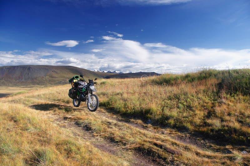 Viaggiatore di enduro del motociclo da solo sotto un cielo blu con le nuvole bianche su un fondo delle montagne con i picchi cope immagini stock libere da diritti