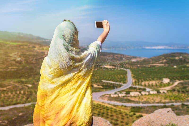 Viaggiatore musulmano della donna in un autoritratto variopinto della presa della sciarpa sullo smartphone sopra una montagna immagine stock libera da diritti