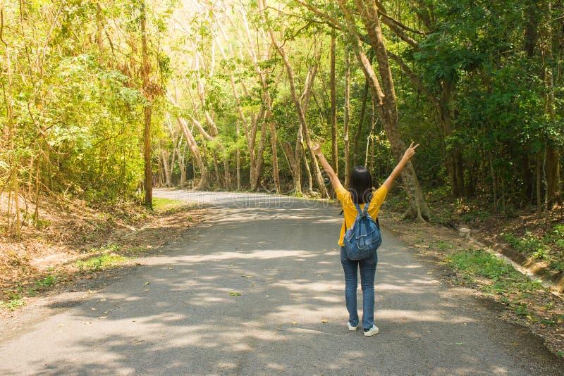 Viaggiatore o viaggiatore con zaino e sacco a pelo solo della donna che cammina lungo la strada di contryside fra gli alberi verd fotografia stock