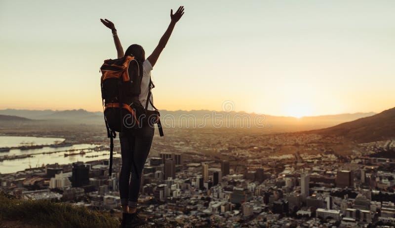 Viaggiatore solo che gode della vista della città dalla cima della collina immagine stock