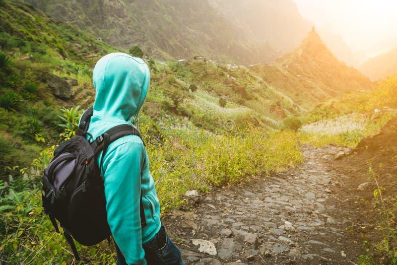 Viaggiatore solo con lo zaino che cammina giù la traccia cobbled di trekking verso la valle verde Il Sun si svasa su hoziron Sant fotografia stock
