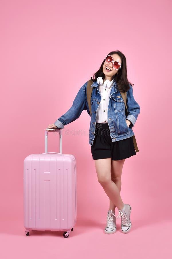 Viaggiatore sorridente della donna che tiene il documento rosa del passaporto e della valigia sopra fondo rosa immagine stock