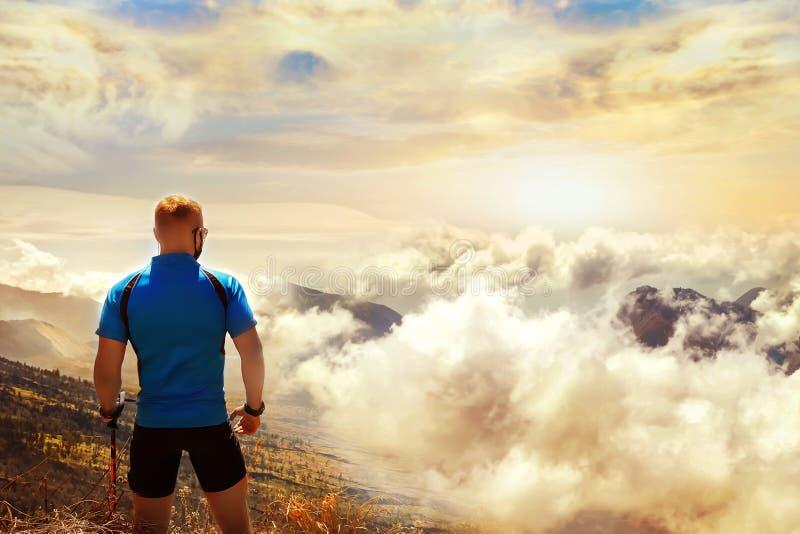 Viaggiatore sportivo del tipo su un fondo di bello cielo con le nuvole al tramonto Vista da sopra immagine stock libera da diritti