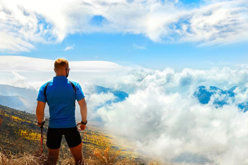 Viaggiatore sportivo del tipo su un fondo di bello cielo con le nuvole nelle montagne Vista da sopra immagine stock libera da diritti