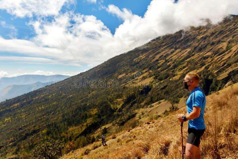 Viaggiatore sportivo del tipo in una maglietta blu su un fondo di bello cielo con le nuvole nelle montagne immagine stock