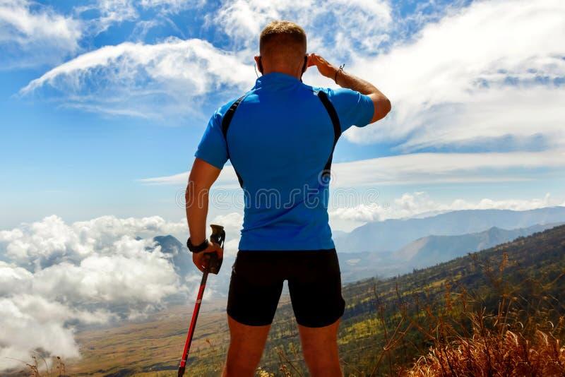 Viaggiatore sportivo del tipo in una maglietta blu su un fondo di bello cielo con le nuvole nelle montagne immagini stock