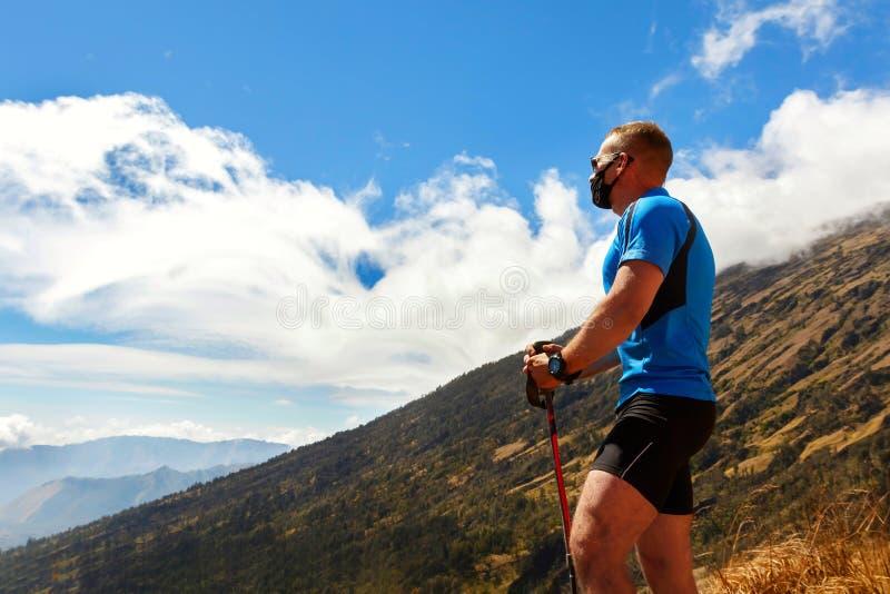 Viaggiatore sportivo del tipo in una maglietta blu su un fondo di bello cielo con le nuvole nelle montagne immagine stock libera da diritti