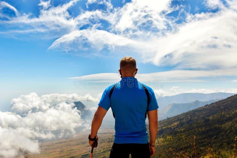 Viaggiatore sportivo del tipo in una maglietta blu su un fondo di bello cielo con le nuvole nelle montagne fotografia stock