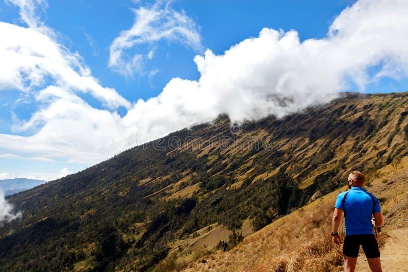 Viaggiatore sportivo del tipo in una maglietta blu su un fondo di bello cielo con le nuvole nelle montagne fotografia stock libera da diritti