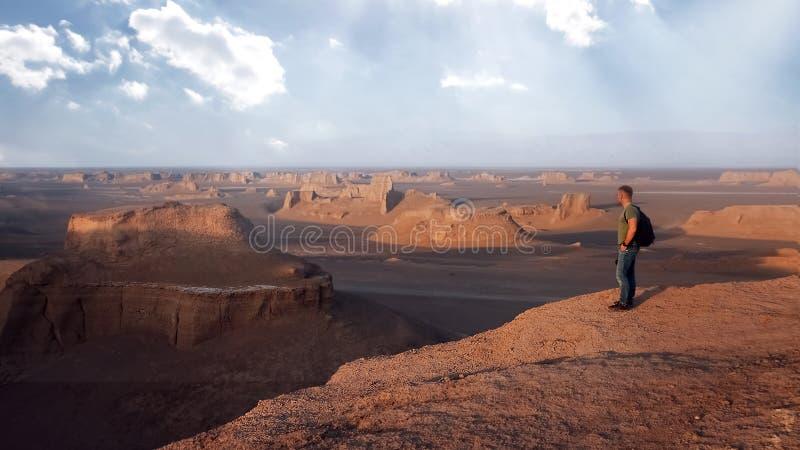 Viaggiatore sui precedenti delle formazioni rocciose nel deserto di Dasht e Lut Caduta di Sheykh Alikhan persia immagine stock libera da diritti