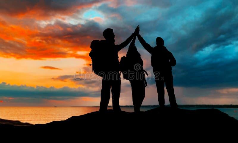 Viaggiatori che fanno su cinque sopra il tramonto fotografia stock