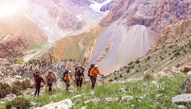 Viaggiatori con zaino e sacco a pelo che camminano sulla traccia di montagna fotografia stock