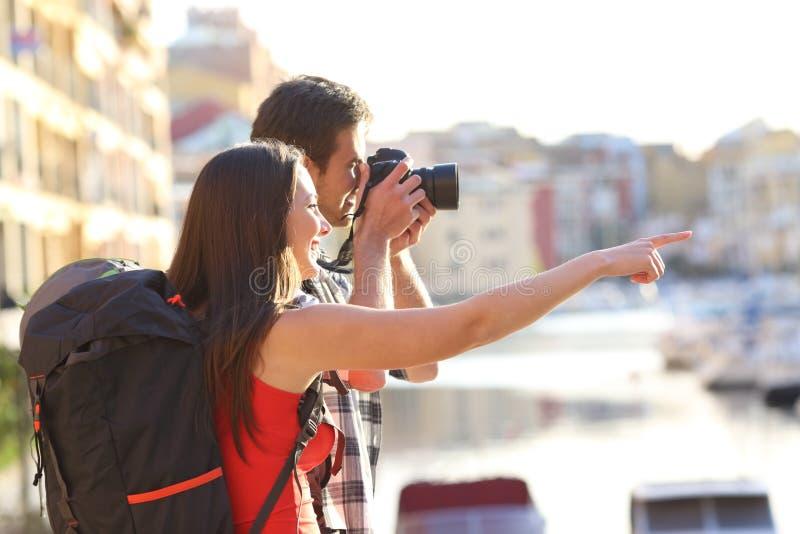 Viaggiatori con zaino e sacco a pelo che prendono le foto sulle vacanze estive immagine stock libera da diritti