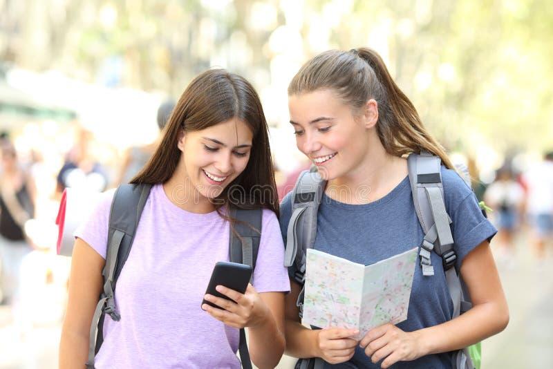 Viaggiatori con zaino e sacco a pelo felici che consultano una guida all'aperto immagini stock
