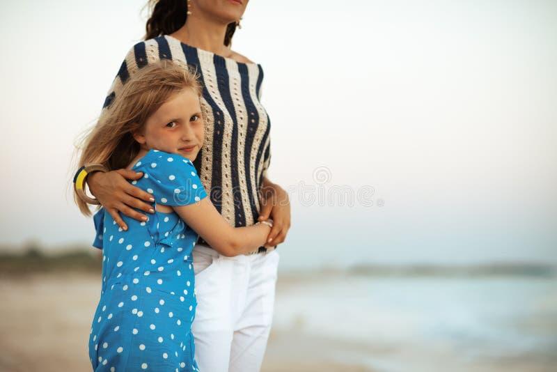 Viaggiatori del bambino e della madre sul litorale all'abbraccio di tramonto immagine stock