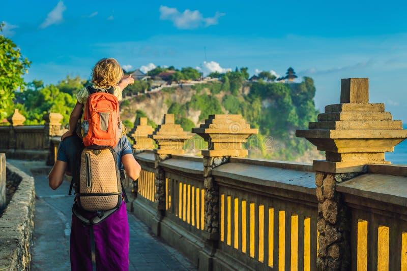 Viaggiatori del figlio e del papà in tempio di Pura Luhur Uluwatu, Bali, Indonesia Paesaggio stupefacente - scogliera con cielo b fotografia stock libera da diritti