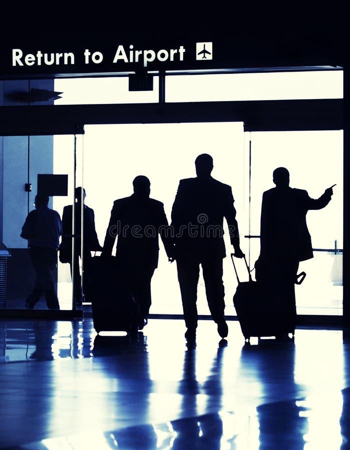 Viaggiatori di affari che escono il terminale di aeroporto. immagine stock