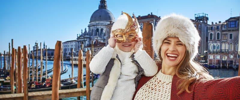 Viaggiatori sorridenti del bambino e della madre che prendono selfie a Venezia immagini stock libere da diritti