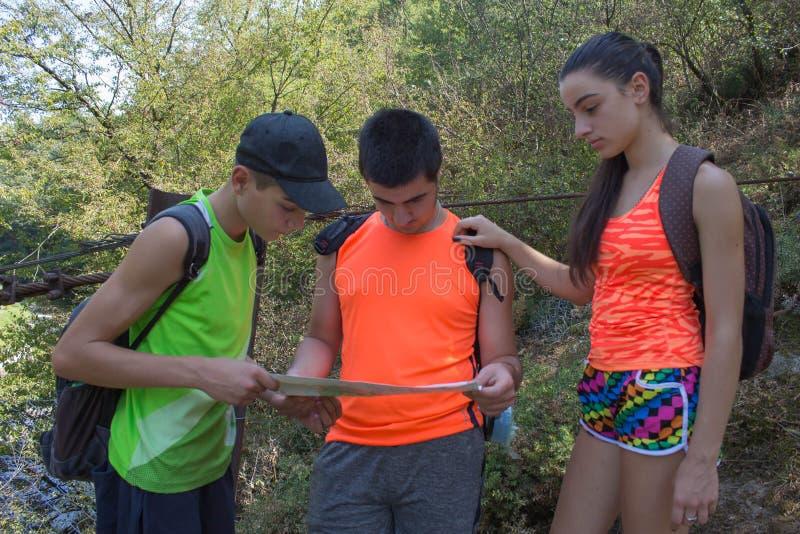 Viaggiatori, viandanti sulla vacanza che leggono una mappa Due giovani turisti con il viaggio degli zainhi Tre giovani turisti co immagini stock