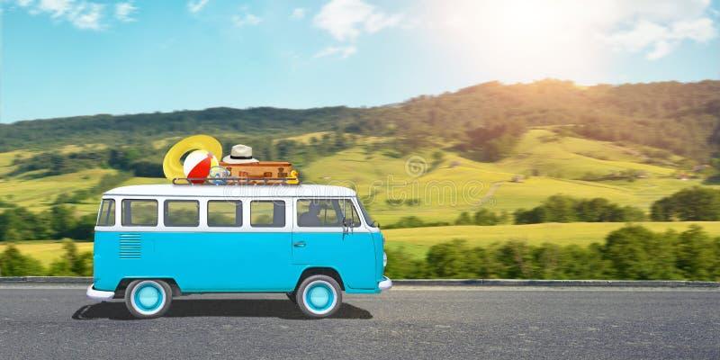Viaggio con un concetto del furgone Il vecchio, blu, furgone di hippy è sulla strada, bagagli è sul tetto fotografie stock