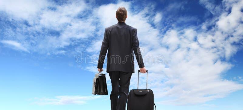 Viaggio dell'uomo di affari con il carrello che cammina al cielo fotografia stock libera da diritti
